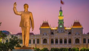 A statue of Ho Chi Minh stands in front.