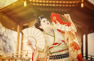 beautiful japanese woman dressed as geisha dancing with fans against Peace Pagoda in Battersea Park in London
